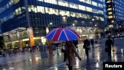 Para pekerja berjalan di tengah hujan di kawasan bisnis Canary Wharf di London, Inggris. (Foto:dok)