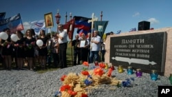 FILE- People attend a memorial service at the crash site of the Malaysia Airlines Flight 17, near the village of Hrabove, eastern Ukraine, July 17, 2015.