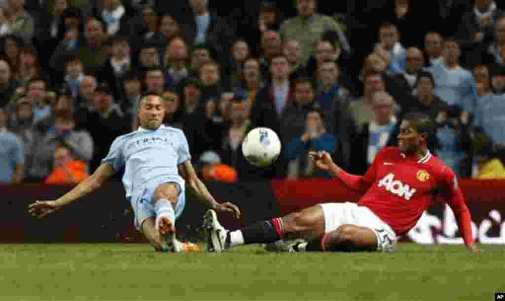 Manchester City's Gael Clichy, left, competes for the ball with Manchester United's Chris Smalling during the English Premier League soccer match between Manchester City and Manchester United at the Etihad Stadium in Manchester, Monday, April 30, 2012. (