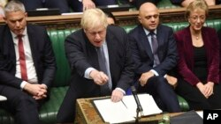 Britain's Prime Minister Boris Johnson speaks to lawmakers inside the House of Commons to update details of his new Brexit deal with EU, in London Saturday Oct. 19, 2019. At a rare weekend sitting of Parliament, Johnson implored legislators to…