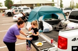 Jackie Armstrong, a Chester resident evacuated from the Dixie Fire, speaks with daughter Zoey Armstrong, 3, at a Susanville, Calif., evacuation shelter, Aug. 6, 2021.
