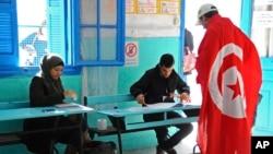 Un Tunisien drapé au drapeau national arrive à un bureau de vote pour voter à La Marsa, dans la banlieue de Tunis, en Tunisie, le 21 décembre 2014.