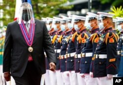FILE - United States Defense Secretary Lloyd Austin views the military honor guard at Camp Aguinaldo military camp in Quezon City, Metro Manila, Philippines.