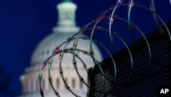 FILE - Riot fencing and razor wire reinforce the security zone on Capitol Hill in Washington, Jan. 19, 2021. Capitol Police say they are stepping up security at D.C.-area transit hubs and taking other steps to bolster travel security for lawmakers.