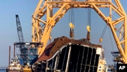 FILE - A towering crane straddles the capsized cargo ship Golden Ray, its interior decks exposed after the ship's bow was cut off and hauled away, off the coast of St. Simons Island, Ga., Feb. 25, 2021.