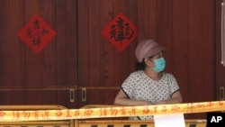 A woman wearing face masks to protect against the spread of the coronavirus lines up at a rapid coronavirus testing center after the COVID-19 alert raise to level 3 in Taipei, Taiwan, Tuesday, May 18, 2021. (AP Photo/Chiang Ying-ying)