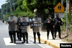 FILE - Nicaraguan police officers block journalists working outside the house of opposition leader Cristiana Chamorro after prosecutors sought her arrest for money laundering and other crimes, in Managua, June 2, 2021.