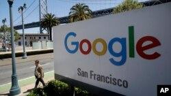 Seorang pria berjalan melewati papan iklan Google di San Francisco, 1 Mei 2019.