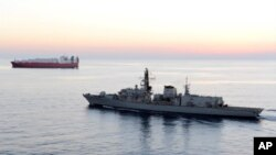 FILE - British navy vessel HMS Montrose escorts a ship at sea off coast of Cyprus in Feb., 2014. The British Navy said it intercepted an attempt, July 11, 2019, by three Iranian paramilitary vessels to impede the passage of a British commercial vessel.