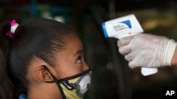 A health worker takes a child's temperature to help curb the spread of the new coronavirus, at the Central de Abasto market in Mexico City, June 18, 2020.