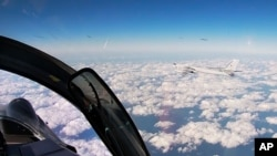 In this photo taken from a video distributed by Russian Defense Ministry Press Service, on Tuesday, Dec. 22, 2020, a Russian Tu-95 strategic bomber flies during a joint patrol mission over the Western Pacific.