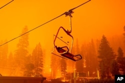 The Caldor Fire burns as a chairlift sits motionless at the Sierra-at-Tahoe ski resort in Eldorado National Forest, Calif., Aug. 29, 2021.