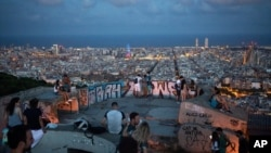People gather outdoors at dusk on a viewpoint in Barcelona, Spain, Saturday, July 25, 2020. Britain is advising people not to travel to Spain and has removed the country from the list of safe places to visit following a surge of COVID-19 cases. (AP…