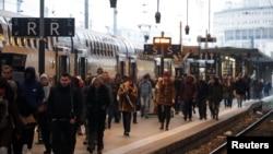 Para penumpang kereta api berjalan di Stasiun Gare de Lyon di Paris ketika pekerja kereta SNCF Prancis dan pekerja transportasi Prancis mogok kerja karena memprotes rencana reformasi pensiun pemerintah Perancis, 6 Desember 2019. (Foto: Reuters)