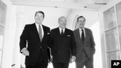 In this Jan. 9, 1985 file photo, Secretary of State George Shultz, center, walks with President Ronald Reagan and Vice President George Bush upon his arrival at the White House in Washington.