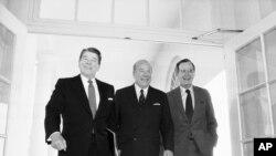 Sur cette photo datant du 9 janvier 1985, le secrétaire d'État George Shultz, au centre, marche avec le président Ronald Reagan et le vice-président George Bush à la Maison Blanche à Washington.