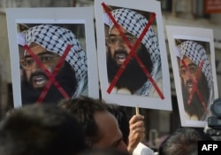 FILE - Indian activists carry placards of the leader of the Pakistan-based Jaish-e-Mohammad group, Masood Azhar, during a protest denouncing the attack on the Indian air force base in Pathankot, in Mumbai, India, Jan. 4, 2016.