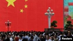 چین کے تجارتی شہر چونگ ژونگ کے ایک کاروباری مرکز میں ایک بڑے پرچم کے سامنے لوگوں کا ہجوم۔ فائل فوٹو