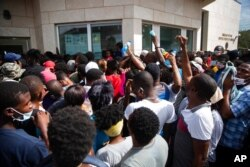Haitians gather in front of the U.S. Embassy amid rumors on radio and social media that the U.S. will be handing out exile and humanitarian visas, in Port-au-Prince, Haiti, July 9, 2021, two days after President Jovenel Moise was assassinated.