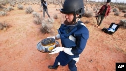 In this photo provided by the Japan Aerospace Exploration Agency (JAXA), a member of JAXA retrieves a capsule dropped by Hayabusa2 in Woomera, southern Australia, Dec. 6, 2020.