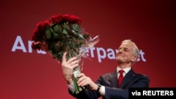 Norway's Labor Party leader Jonas Gahr Stoere holds a bouquet of red roses at the Labor Party's election vigil at the People's House during parliamentary elections in Oslo, Norway, September 13, 2021. (Javad Parsa/NTB via Reuters)