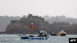 French fishing boats protest in front of the port of Saint Helier off the British island of Jersey to draw attention to what they see as unfair restrictions on their ability to fish in UK waters after Brexit, on May 6, 2021.