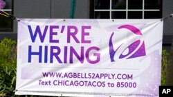 FILE - A hiring sign is displayed outside a restaurant during the COVID-19 pandemic in Glenview, Ill., May 8, 2021.