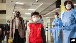 Passengers arriving from a China Southern Airlines flight from Changsha in China are screened for the new type of coronavirus, whose symptoms are similar to the cold or flu and many other illnesses, upon their arrival at the Jomo Kenyatta…