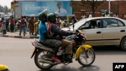 FILE - A passenger rides on a moto-taxi in Kigali, Rwanda, July 30, 2017. Rwanda is introducing electric motorcycles, with more than 600 being built for use in the country.