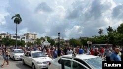El pueblo se acerca a los autos policiales durante las manifestaciones ocurridas en Cuba el 11 de julio de 2021. En la imagen parte de los sucesos frente al Capitolio de La Habana, la capital.