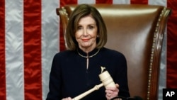House Speaker Nancy Pelosi of Calif., smiles as she holds the gavel as the House votes on articles of impeachment against President Donald Trump by the House of Representatives at the Capitol in Washington, Dec. 18, 2019.