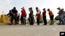 FILE - Migrants seeking asylum in the United States line up for a meal provided by volunteers near the international bridge in Matamoros, Mexico, April 30, 2019.