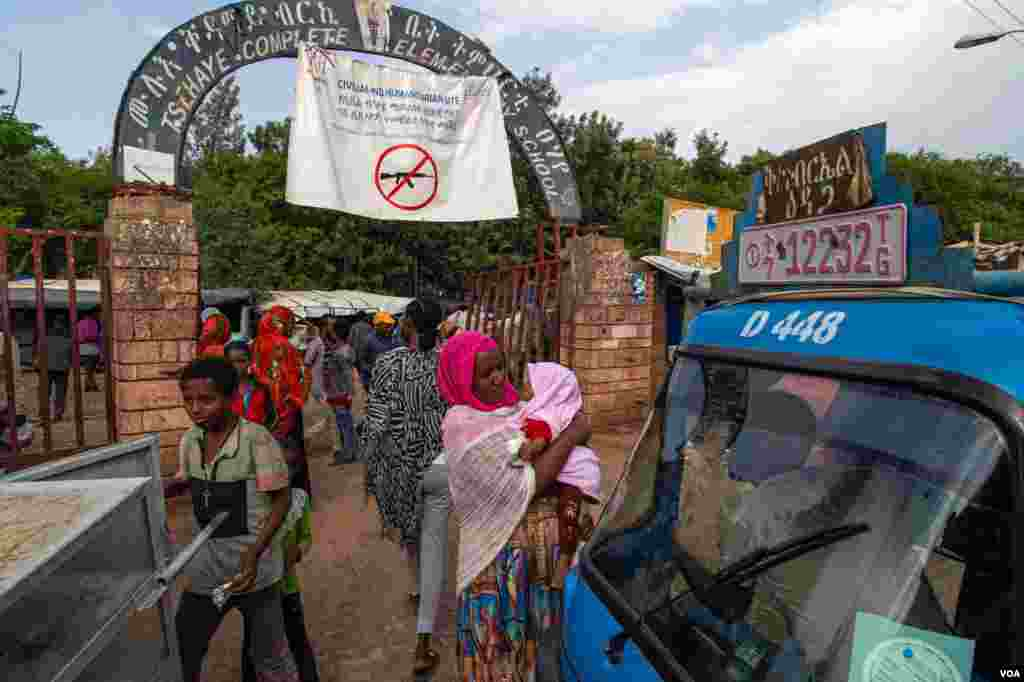The busy entrance of a crowded school that has been converted into a camp for displaced families in Shire, June 11, 2021 (Yan Boechat/VOA)