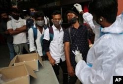A health worker in protective suit collects nasal swab sample of a traveler to test for COVID-19 outside a train station in Bengaluru, India, June 16, 2021.