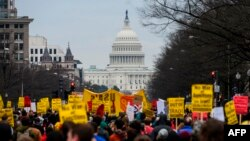 Anti-war activist march from the White House to the Trump International Hotel in Washington, DC, on January 4, 2020. - Demonstrators are protesting the US drone attack which killed Iran's Major General Qasem Soleimani in Iraq on January 3, a…