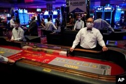 FILE - Dealers in masks wait for customers at the D Las Vegas hotel and casino in Las Vegas, June 3, 2020.