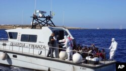 Migrants are evacuated by Italian Coast guards from the Open Arms Spanish humanitarian boat at the coasts of the Sicilian island of Lampedusa, southern Italy, Aug.17, 2019.