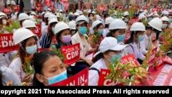 2021年2月21日在曼德勒举行的反政变游行中,医学院学生戴着口罩,举着标语牌聚集在一起。