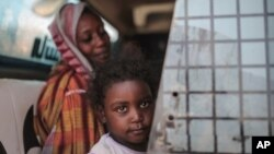 Seorang ibu dan anak perempuannya tengah menunggu bus di Izba, dekat Khartoum, Sudan, 14 Apri 2015. (Foto: dok).