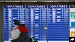 FILE - People embrace in front of a flight departures board at Dulles International Airport in Dulles, Va., March 17, 2020. At least 15 VOA journalists are to return to their country of origin in coming weeks, after USAGM did not renew their J-1 visas.