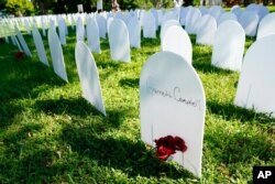White plastic tombstone-shaped pieces are lined up as a temporary memorial to some of Miami's victims of the coronavirus at Simonhoff Floral Park, Oct. 14, 2020, in the Liberty City neighborhood of Miami.