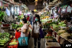 A customer walks through a wet market wearing a protective face mask in Hong Kong on Feb. 25, 2020.