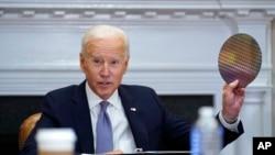 美國總統拜登在白宮羅斯福廳在線參加半導體和供應鏈復原力CEO峰會時,舉起一塊矽片(2021年4月12日)。