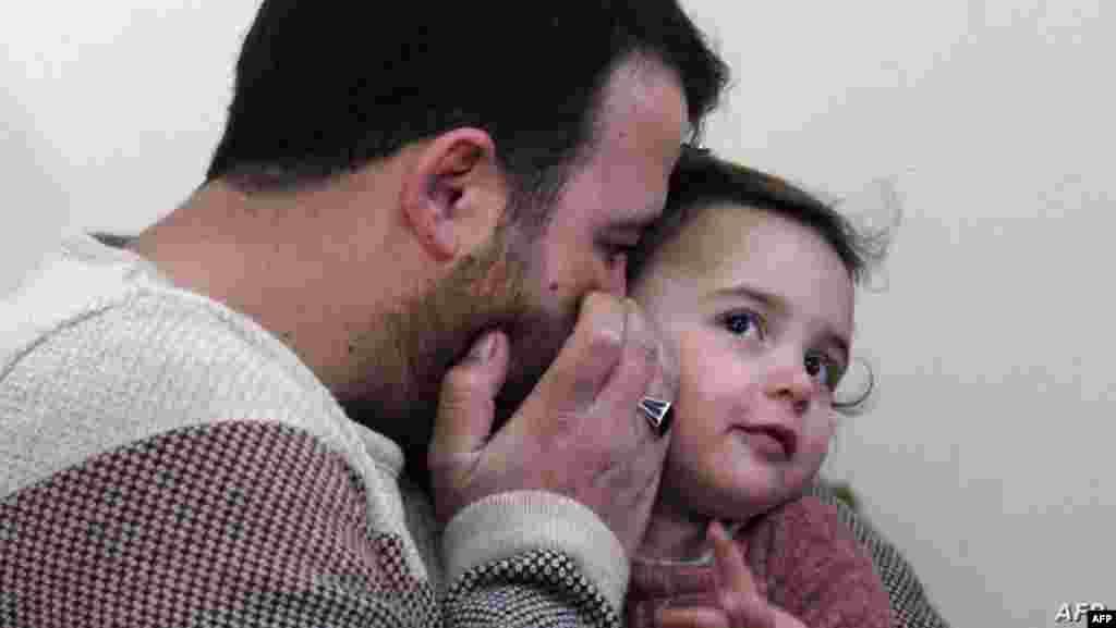 시리아 북서부 이들리브주 사르마다에서 압둘라알모하마드가 3살 딸 살와에게 귓속말을 하고 있다.