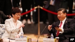 FILE - China's President Xi Jinping, right, and Hong Kong's Chief Executive Carrie Lam talk during the APEC-ASEAN dialogue, on the sidelines of the APEC summit, in Danang, Vietnam, Nov. 10, 2017.