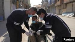 شام کے شہر قامشلی میں لاک ڈاؤن کے دوران ریسکو ورکر ایک شخص کو وہیلز چیئر پر اسپتال لے جا رہے ہیں۔ 23 مارچ 2020