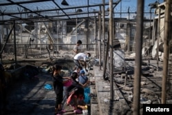 Refugees and migrants gather water next to destroyed shelters following a fire at the Moria camp on the island of Lesbos, Greece, Sept. 9, 2020.