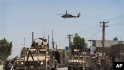 Tentara AS dan kendaraan berlapis baja mereka mengamankan jalanan di depan kompleks rumah Gubenur Kandahar, Sabtu (28/4).