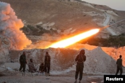 FILE - Free Syrian Army fighters launch a Grad rocket from Halfaya town in Hama province, towards forces loyal to Syria's President Bashar al-Assad stationed in Zein al-Abidin mountain, Syria, Sept. 4, 2016.
