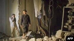 Các nhân viên Libya đang xem xét thiệt hại của một tòa nhà sau khi bị oanh kích ở Tripoli, Libya, sáng sớm ngày 30 tháng 4, 2011